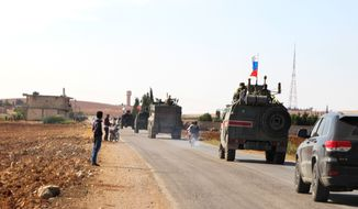 Russian forces armored vehicles patrol the Syrian border in Kobani, Wednesday, Oct. 23, 2019. Russian military police began patrols on part of the Syrian border Wednesday, quickly moving to implement an accord with Turkey that divvies up control of northeastern Syria. (AP Photo)