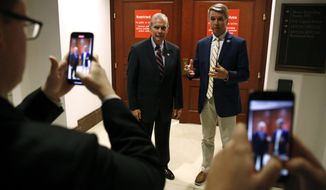 Rep. Tim Walberg, R-Mich., left, and Rep. Rob Wittman, R-Va., film a video in front of an entrance to a secure area after Deputy Assistant Secretary of Defense Laura Cooper arrived for a closed door meeting to testify as part of the House impeachment inquiry into President Donald Trump, Wednesday, Oct. 23, 2019, on Capitol Hill in Washington. (AP Photo/Patrick Semansky)