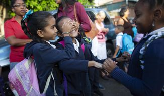 In this October 2, 2019 photo, girls play as they wait to enter on their first day of school, in Caracas, Venezuela. The school year recently began amid the once-wealthy country's deepening crisis, with more teachers and students abandoning their homeland, leaving classrooms empty. (AP Photo/Ariana Cubillos)