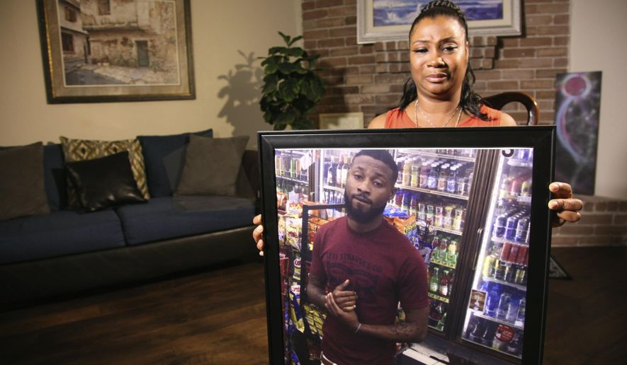 In this Monday, Aug. 19 2019, photo, Yvonne Ferguson-Smith, holds up a framed photo of her deceased son, Kenneth Roberson, at her Missouri City, Texas home. Ferguson-Smith, talked with The Associated Press about her son's 2018 death by a drive-by shooting, a crime which police believed they solved by a city wide bullet image database that tied the guns used in the murder to two known Houston gang members. (AP Photo/ John L. Mone)