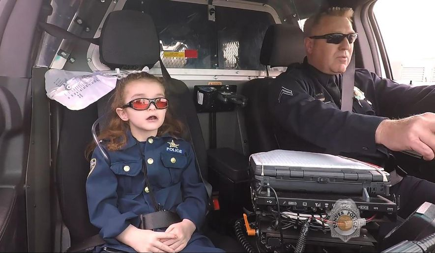 In this image made from April 2017 video provided by the Denver Police Department, Olivia Gant, who was 6 years old at the time, rides with Cpt. Tim Scudder on a call in Denver. On Monday, Oct. 21, 2019, a Douglas County, Colo., grand jury indicted the mother of Olivia Gant in connection with the little girl's 2017 death. Olivia's mother, Kelly Renee Turner, faces 13 charges, including first-degree murder. Olivia Gant was riding in the police car after Denver police made her an officer for a day. (Denver Police Department/The Denver Post via AP)