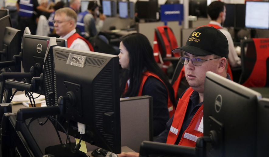 FILE - In this Oct. 10, 2019, file photo, Pacific Gas & Electric employees work in the PG&E Emergency Operations Center in San Francisco. Authorities say power outages have started Wednesday, Oct. 23, 2019, in Northern California after the state's largest utility said it was planning a widespread blackout citing wildfire danger. The Santa Rosa Fire Department tweeted Wednesday that shutoffs had started in the city and it was getting multiple reports of outages. Pacific Gas & Electric said earlier Wednesday it was going forward with blackouts later in the day that could affect 450,000 people in 17 counties of Northern California. (AP Photo/Jeff Chiu, File)