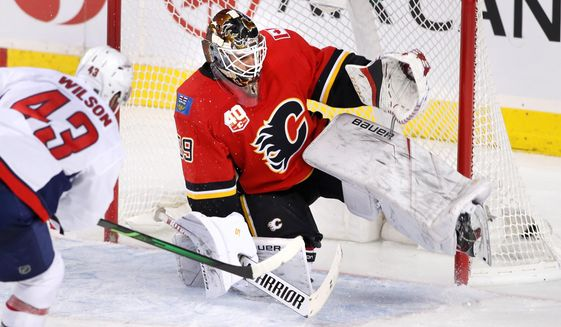 Washington Capitals right wing Tom Wilson (43) scores on Calgary Flames goaltender Cam Talbot during the third period of an NHL hockey game Tuesday, Oct. 22, 2019, in Calgary, Alberta. (Larry MacDougal/The Canadian Press via AP)