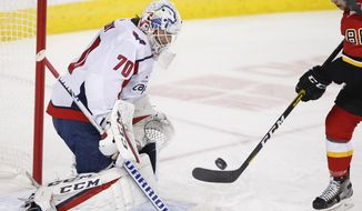 Washington Capitals goalie Brayden Holtby makes a save against Calgary Flames' Andrew Mangiapane during the first period of an NHL hockey game Tuesday, Oct. 22, 2019, in Calgary, Alberta. (Larry MacDougal/The Canadian Press via AP) ** FILE **