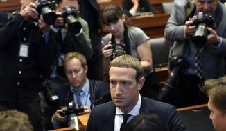 Facebook Chief Executive Officer Mark Zuckerberg, front right, is surrounded by photographers after arriving for a hearing before the House Financial Services Committee on Capitol Hill in Washington, Wednesday, Oct. 23, 2019, to discuss his plans for the new cryptocurrency Libra. (AP Photo/Susan Walsh)