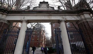 In this Dec. 13, 2018, file photo, people walk through the gates leading to Harvard Yard at Harvard University in Cambridge, Mass. Harvard's student newspaper is facing a campus backlash over a routine request for government comment about a student demonstration against U.S. Immigration and Customs Enforcement. (AP Photo/Charles Krupa, file) ** FILE **