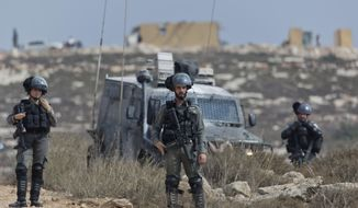 Israeli border police secure a road leading to a newly established Israeli settlers outpost, seen in the background, during clashes with Palestinian protesters in the West Bank village of Tormusayya, northeast of Ramallah, Thursday, Oct. 17. 2019. Palestinian protesters marched toward a newly established Israeli settlers outpost on the outskirts of the Palestinian village of Tormusayya, before clashing with Israeli forces blocking the road leading to the outpost. (AP Photo/Nasser Nasser)