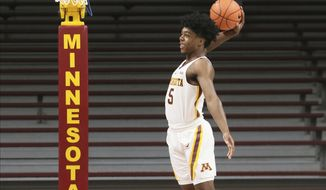 In this Oct. 18, 2019 photo, Minnesota guard Marcus Carr poses for a photo shoot during Minnesota's NCAA college basketball media day in Minneapolis. Carr, who played last season for Pittsburgh, is one of three transfers to Minnesota eligible to play this season as Minnesota must replace its two best players in Jordan Murphy and Amir Coffey. (AP Photo/Jim Mone)