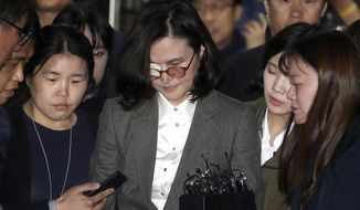 In this Wednesday, Oct. 23, 2019, photo, Chung Kyung-shim, center, the wife of South Korea's former Justice Minister Cho Kuk, leaves the Seoul Central District Court in Seoul, South Korea. Prosecutors on Thursday, Oct. 24, 2019 arrested the wife of Cho who resigned last week over corruption allegations surrounding his family that have sparked huge protests and rattled Seoul's liberal government. (Park Mi-so/Newsis via AP)