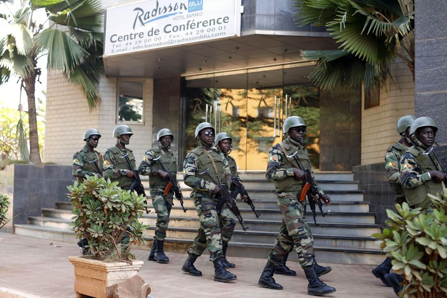 In this Saturday, Nov. 21, 2015, file photo, soldiers from the presidential guard patrol outside the Radisson Blu hotel in Bamako after it was attacked by Islamic extremists armed with guns and grenades. Islamic extremists have displaced half a million people this year in the border area between Burkina Faso and Mali as their threat continues to spread in West Africa's Sahel region. The fighters linked to al Qaeda and the Islamic State group are exploiting military and government weaknesses as well as local grievances. A regional counterterror force has failed to stop the attacks and has become a target itself. (AP Photo/Jerome Delay, File)