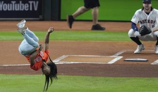 Gymnast Simone Biles does a flip before throwing the ceremonial first pitch before Game 2 of the baseball World Series between the Houston Astros and the Washington Nationals Wednesday, Oct. 23, 2019, in Houston. (AP Photo/Eric Gay) ** FILE **