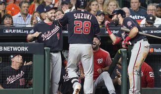 Washington Nationals' Kurt Suzuki is congratulated after hitting a home run during the seventh inning of Game 2 of the baseball World Series against the Houston Astros Wednesday, Oct. 23, 2019, in Houston. (AP Photo/David J. Phillip)