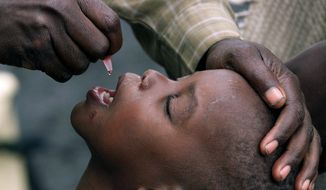FILE -- In this Jan. 25 , 2002 file photo, a Congolese child is given a polio vaccination at a relief camp near Gisenyi, Rwanda. The World Health Organization says Zambia has reported its first local case of polio since 1995 in a 2-year-old boy paralysed by a virus derived from the vaccine. (AP Photo/Karel Prinsloo, File)