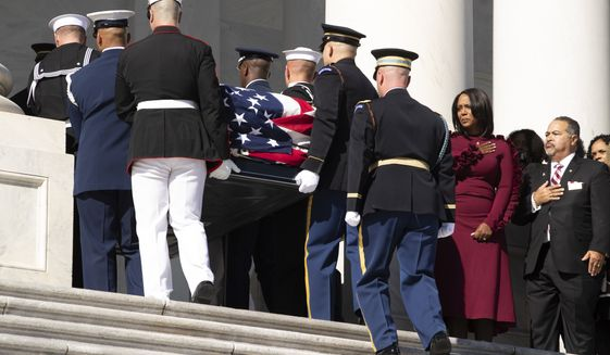 The casket of Rep. Elijah Cummings is carried up the East Front steps of the U.S. Capitol, as widow Maya Rockeymoore, second from right and family members watch Thursday, Oct. 24, 2019, in Washington. (Michael Reynolds/Pool via AP)