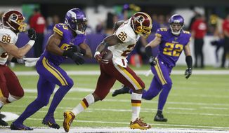 Washington Redskins running back Adrian Peterson (26) runs from Minnesota Vikings defensive end Danielle Hunter (99) during the second half of an NFL football game, Thursday, Oct. 24, 2019, in Minneapolis. (AP Photo/Jim Mone)