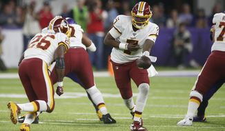 Washington Redskins quarterback Dwayne Haskins (7) hands the ball off to running back Adrian Peterson, left, during the second half of an NFL football game against the Minnesota Vikings, Thursday, Oct. 24, 2019, in Minneapolis. (AP Photo/Jim Mone) ** FILE **