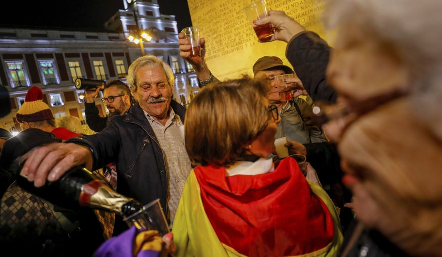 People celebrate the exhumation of late Spanish dictator Gen. Francisco Franco in Madrid, Thursday, Oct. 24, 2019. Spain has exhumed the remains of Spanish dictator Gen. Francisco Franco from his grandiose mausoleum outside Madrid and flown them by helicopter for reburial in a small family crypt north of the capital. The government-ordered, closed-door operation on Thursday satisfies a decades-old desire of many in Spain who considered the vainglorious mausoleum that Franco built an affront to the tens of thousands who died in Spain's Civil War and his subsequent regime as well as to Spain's standing as a modern democratic state. (AP Photo/Bernat Armangue)
