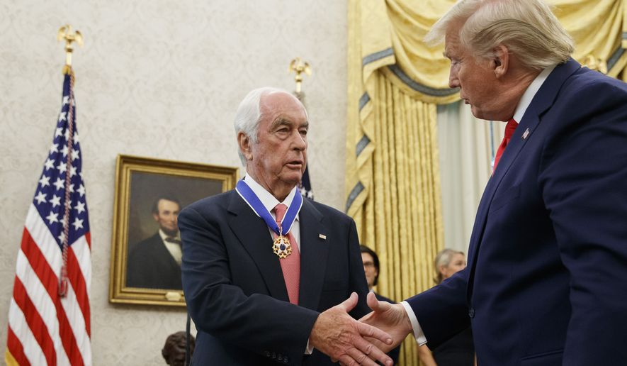 President Donald Trump shakes hands with auto racing great Roger Penske during a Presidential Medal of Freedom ceremony in the Oval Office of the White House, Thursday, Oct. 24, 2019, in Washington. (AP Photo/Alex Brandon)