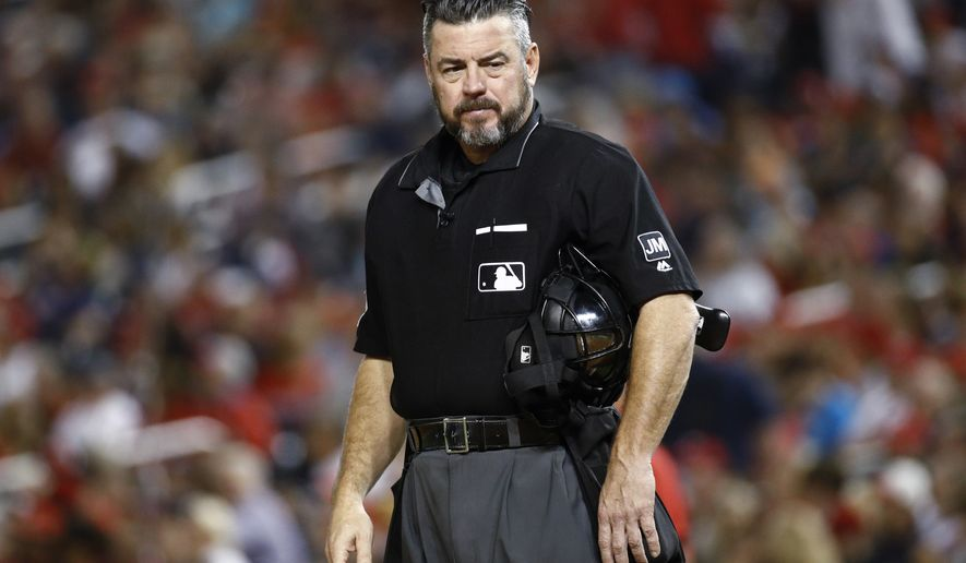 In this Sept. 13, 2019, file photo, umpire Rob Drake stands on the field during a baseball game between the Atlanta Braves and the Washington Nationals in Washington. Commissioner Rob Manfred says Major League Baseball will look into a politicized tweet by Drake that referenced a rifle and criticism of President Donald Trump. (AP Photo/Patrick Semansky, File)