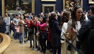 """Tourists take snapshot of the Leonardo da Vinci's painting Mona Lisa, at the Louvre museum, in Paris, Wednesday, Oct. 23, 2019. The Louvre, the home of the """"Mona Lisa,"""" is commemorating the 500th anniversary of Leonardo Da Vinci's death with a landmark new exhibit. (AP Photo/Thibault Camus)"""