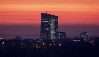 The sky is orange over the European central Bank in Frankfurt, Germany, before sunrise on Tuesday, Oct. 22, 2019. (AP Photo/Michael Probst)
