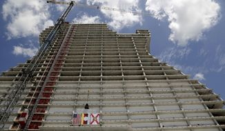 """FILE - In this July 9, 2018 file photo, two of the final steel beams with signatures along with the American, Seminole Tribe, and the State flags are hoisted during the """"Topping Out"""" ceremony where the beams of the highly anticipated project were ceremonially set atop the giant framework of the guitar shaped tower in Hollywood, Fla. It looks like the guitar Led Zeppelin's Jimmy Page played. But this one is 450 feet (137 meters) tall and is a light-beam hotel that the Seminole Tribe wants to become South Florida's latest tourist destination. The Guitar Hotel's grand opening is Thursday, Oct. 24, 2019, on the tribe's land in Hollywood. It's the latest step in the Seminole Hard Rock empire, which includes naming rights on the Miami-area stadium where the 2020 Super Bowl will be played. (Carl Juste/Miami Herald via AP, File)"""