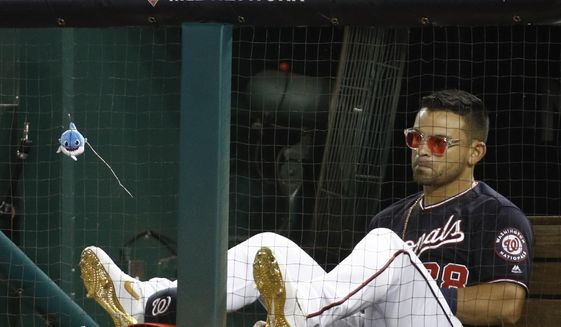 Washington Nationals' Gerardo Parra sits in the dugout with a toy shark hanging from the net during the fourth inning of Game 4 of the baseball National League Championship Series against the St. Louis Cardinals Tuesday, Oct. 15, 2019, in Washington. (AP Photo/Patrick Semansky)