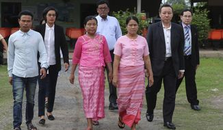 Phyu Shwe Nu, mother of Myanmar Zaw Lin, center left, and May Thein, mother of Myanmar Wai Phyo, center right, arrive for petition royal pardon at Bangkwang prison on the outskirts of Bangkok, Thailand, Thursday, Oct. 24, 2019. The families of two Myanmar migrant workers sentenced to death for the brutal murders of two British tourists in Thailand in 2014 have appealed to the Thai king to spare their lives. (AP Photo/Sakchai Lalit)