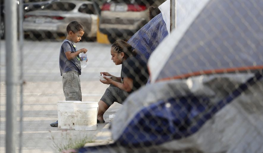 Suanny Gomez, 24, from Honduras and seeking asylum in the United States, waits in a tent with her 5-year-old son, William, Tuesday, April 30, 2019, in Matamoros, Mexico. Gomez said she does not have money to pay a proposed fee for seeking asylum. (AP Photo/Eric Gay)
