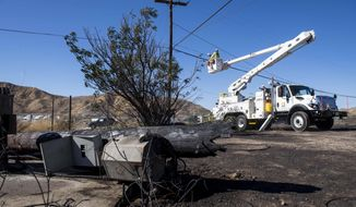 SoCal Edison workers replace power lines that were damaged from the Tick Fire, Thursday, Oct. 25, 2019, in Santa Clarita, Calif. An estimated 50,000 people were under evacuation orders in the Santa Clarita area north of Los Angeles as hot, dry Santa Ana winds howling at up to 50 mph (80 kph) drove the flames into neighborhoods (AP Photo/ Christian Monterrosa)