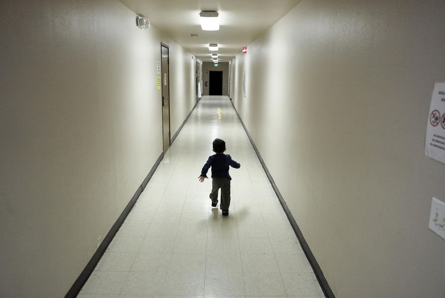 In this Dec. 11, 2018 file photo, an asylum-seeking boy from Central America runs down a hallway after arriving from an immigration detention center to a shelter in San Diego. (AP Photo/Gregory Bull) **FILE**