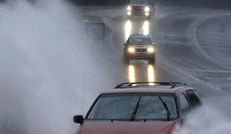 Cars travel along a partially flooded road in Helena, Ala., on Friday, Oct. 25, 2019. The National Weather Service said a disturbance in the Gulf of Mexico that could briefly become a tropical weather system was combining with a cold front to dump heavy rains across the parched region. (AP Photo/Jay Reeves)