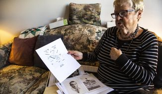 """Marilea Schmidt speaks about the Bataan Death March, while looking through photos of her uncle William """"Bill"""" Querl from a folder of images, Thursday, Oct., 17, 2019, at her apartment in Marion, Iowa. (Joseph Cress/Iowa City Press-Citizen via AP)"""