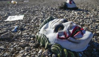 Halloween masks litter the ground amongst signs of chaos at the scene where a mass shooting occurred the night before at Party Venue on Highway 380 in Greenville, Texas, on Sunday, October 27, 2019. As of early Sunday morning a gunman is still at large after killing at least two people and injuring 14 at Party Venue Saturday night, according to Chief Deputy Buddy Oxford of the Hunt County Sheriff's Department. (Ryan Michalesko/The Dallas Morning News via AP)