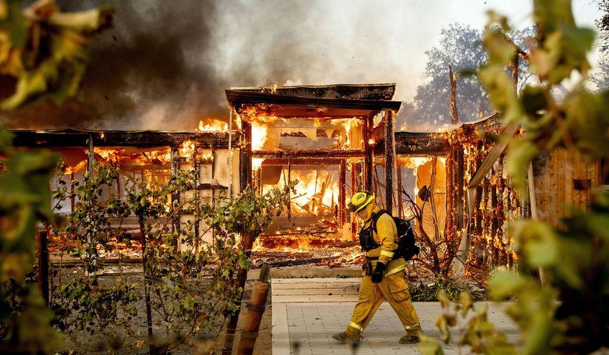 Woodbridge firefighter Joe Zurilgen passes a burning home as the Kincade Fire rages in Healdsburg, Calif., on Sunday, Oct 27, 2019. (AP Photo/Noah Berger)