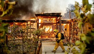 Woodbridge firefighter Joe Zurilgen passes a burning home as the Kincade Fire rages in Healdsburg, Calif., on Sunday, Oct 27, 2019. (AP Photo/Noah Berger)