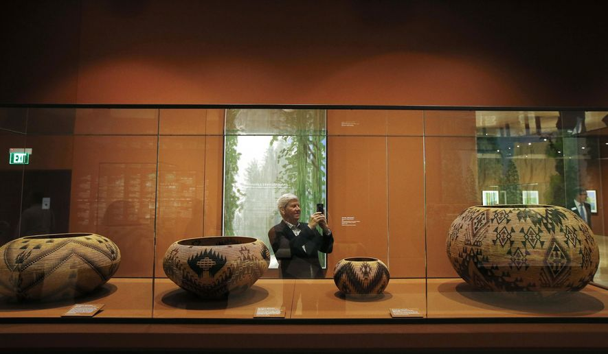 """In this Wednesday, Oct. 23, 2019, photo, Richard Benefield, former executive director of the David Hockney Foundation, takes a photo inside the exhibit of Hockney's Yosemite artistic work, background, along with baskets from weavers from the Miwok and Mono Lake Paiute tribes on display at the Heard Museum in Phoenix. """"David Hockney's Yosemite and Masters of California Basketry"""" exhibition opens Monday. (AP Photo/Ross D. Franklin)"""