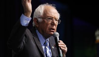 """Democratic presidential candidate Sen. Bernie Sanders, I-Vt., speaks at the J Street National Conference, with the hosts of """"Pod Save the World,"""" Tommy Vietor, left, and Ben Rhodes, Monday, Oct. 28, 2019, in Washington. (AP Photo/Jacquelyn Martin)"""