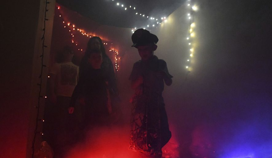 Trick-or-treaters work their way through a haunted-house attraction in Johnstown, Pa., in this Oct. 28, 2019 file photo.  (John Rucosky/The Tribune-Democrat via AP) **FILE**