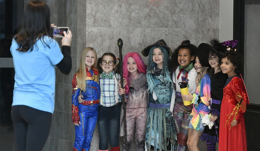 Divine Mercy Catholic Academy teacher Carrie Basile takes a photo of students before they march in the annual Halloween parade at Johnstown Galleria in Johnstown, Pa., on Monday, Oct. 28, 2019. (Todd Berkey/The Tribune-Democrat via AP)