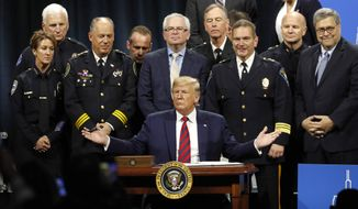 President Donald Trump solicits response from the crowd before signing an executive order creating a commission to study law enforcement and justice at the International Association of Chiefs of Police Convention Monday, Oct. 28, 2019, in Chicago. (AP Photo/Charles Rex Arbogast)
