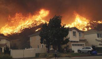 A wildfire approaches a residential subdivision Oct. 24, 2019, in Santa Clarita, Calif. (AP Photo/Marcio Jose Sanchez)