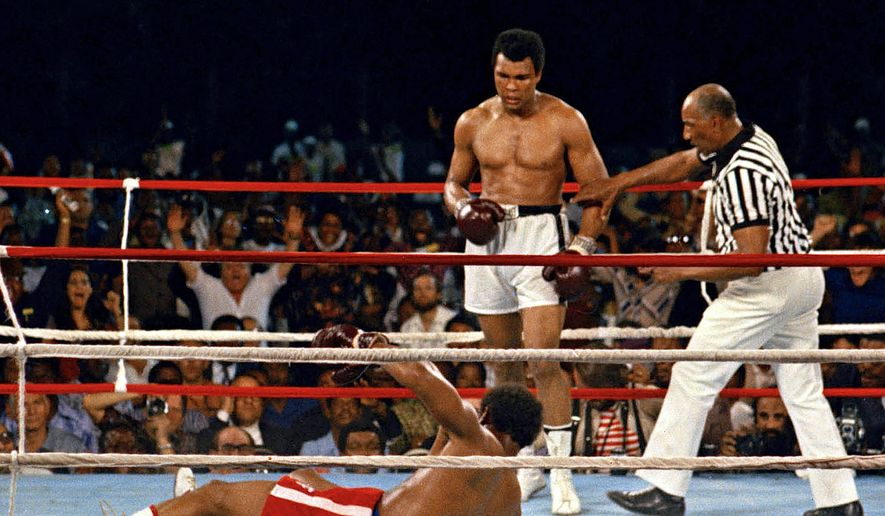 "In this Oct. 30, 1974 file photo, referee Zack Clayton, right, steps in after challenger Muhammad Ali looks on after knocking down defending heavyweight champion George Foreman in the eighth round of their championship bout in Kinshasa, Zaire. Ali regained the world heavyweight crown by knockout in the eighth round of the fight dubbed ""Rumble in the Jungle."" (AP Photo/File) **FILE**"