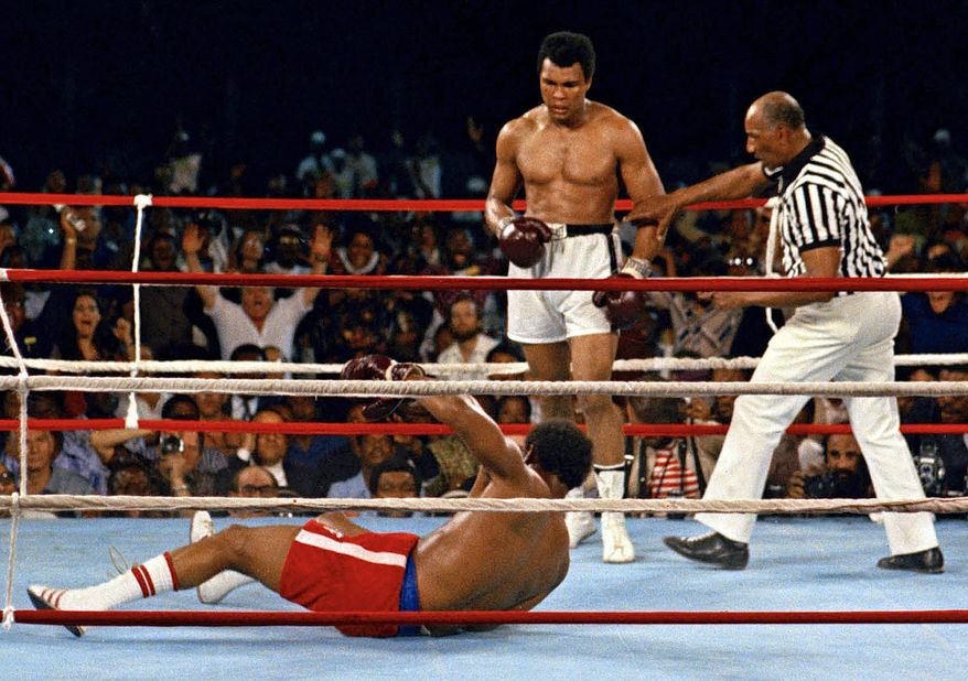 """In this Oct. 30, 1974 file photo, referee Zack Clayton, right, steps in after challenger Muhammad Ali looks on after knocking down defending heavyweight champion George Foreman in the eighth round of their championship bout in Kinshasa, Zaire. Ali regained the world heavyweight crown by knockout in the eighth round of the fight dubbed """"Rumble in the Jungle."""" (AP Photo/File) **FILE**"""