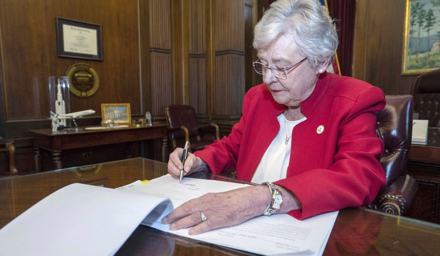 This Wednesday, May 15, 2019, photo released by the state shows Alabama Gov. Kay Ivey signing a bill that virtually outlaws abortion in the state, in Montgomery, Ala. U.S. District Judge Myron Thompson on Tuesday, Oct. 29, 2019, has blocked an Alabama abortion ban that would have made the procedure a felony at any stage of pregnancy in almost all cases. (Hal Yeager/Alabama Governor's Office via AP) **FILE**