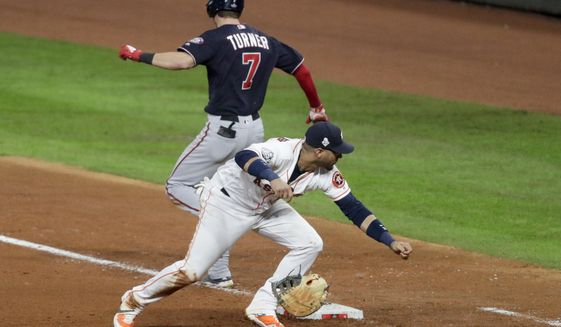 Washington Nationals' Trea Turner knocks the glove away from Houston Astros first baseman Yuli Gurriel during the seventh inning of Game 6 of the baseball World Series Tuesday, Oct. 29, 2019, in Houston. (AP Photo/Sue Ogrocki)