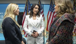 Democratic presidential candidate U.S. Rep. Tulsi Gabbard, center, D-Hawaii, talks to Kaitlyn, left and her mother Terry Strada whose father Tom died during the terrorist attack on 9/11 during a news conference at the 9/11 Tribute Museum, Tuesday, Oct. 29, 2019, in New York. (AP Photo/Mary Altaffer)