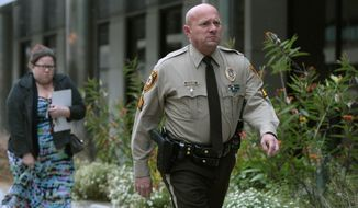 """FILE - In this Oct. 24, 2019 file photo, St. Louis County police Sgt. Keith Wildhaber returns from lunch break to the St. Louis County courthouse on the third day of his discrimination case against the county in Clayton, Mo. Some St. Louis County leaders are calling for a police leadership shakeup after a jury found that Wildhaber was discriminated against because he's gay and recommended that he be awarded nearly $20 million. Councilwoman Lisa Clancy says Police Chief Jon Belmar should resign because of what she described as a """"culture of rampant racism and homophobia."""" (Cristina M. Fletes/St. Louis Post-Dispatch via AP, File)"""