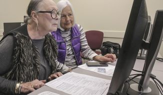 In this Monday, Oct. 28, 2019 photo, Judy Harbour, left, fills out a substitute teacher job application at the Little Rock School District's Technology Center on Scott Hamilton Road in Little Rock . Harbour brought along her friend Katsy Morris, right, who is visiting from San Antonio. The district held a hiring event all day Monday, that will continue today from 10 a.m. to 630 p.m. Little Rock is preparing for a possible teacher strike. (John Sykes Jr./The Arkansas Democrat-Gazette via AP)