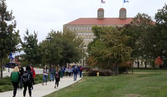 In this Oct. 24, 2019, file photo students walks in front of Fraser Hall on the University of Kansas campus in Lawrence, Kan. (AP Photo/Orlin Wagner, File)